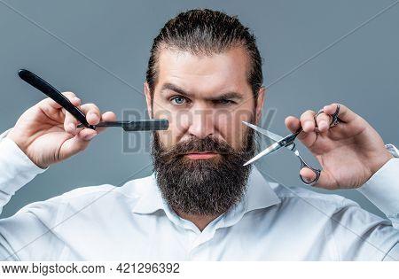Brutal Guy, Scissors, Straight Razor. Bearded Client Visiting Barber Shop. Barber Scissors And Strai