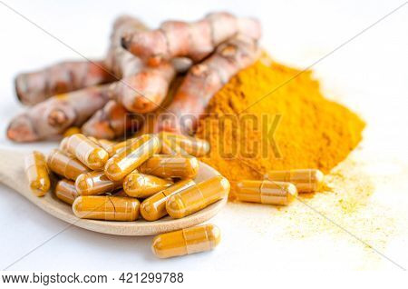 Closed Up Turmeric Or Curcumin Powder In Capsule On Wooden Spoon, Over Blur Background Of Fresh Turm