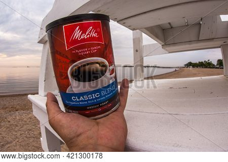 Hand holding Melitta Classic Blend coffee can on beach