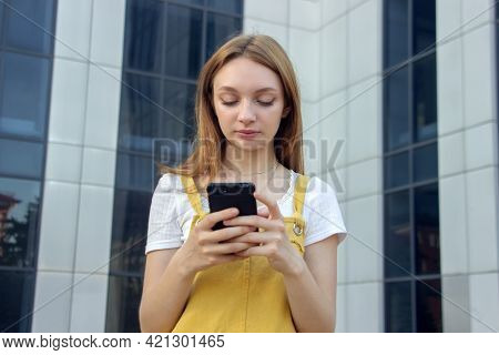 The Girl Is Typing Sms. Teenager With The Phone. Youth And Technology. Communication Through Corresp
