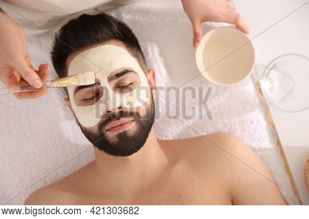 Cosmetologist Applying Mask On Man's Face In Spa Salon, Top View