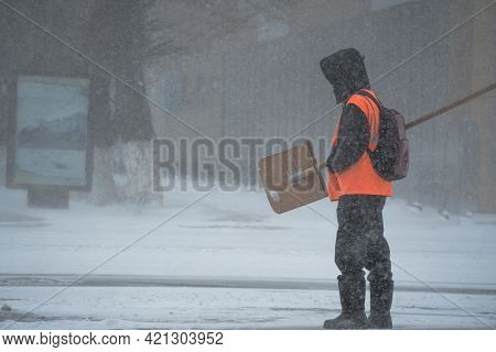 A Working Man Of The Municipal Service With A Snow Shovel Walks Along The Road In A Storm, Blizzard