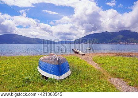 Spring Mediterranean Landscape With Fishing Boat On Green Grass Near Water. Montenegro, Adriatic Sea