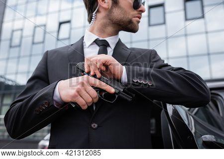 Side View Of Bearded Bodyguard In Suit Holding Gun Near Modern Building.