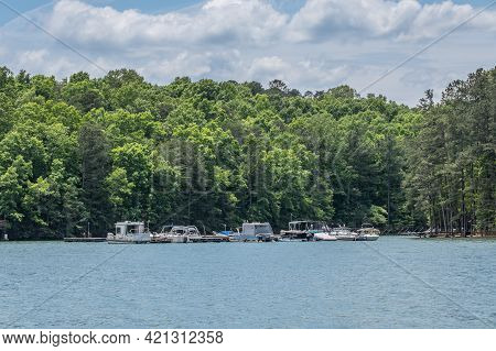 Variety Of Small Boats Moored At A Floating Dock On The Lake In The Inlet On A Sunny Day In Springti