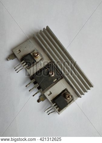 Three Old Transistors On An Aluminum Radiator On A White Background