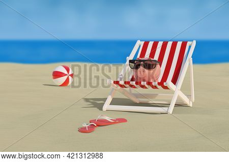 Piggy Bank With Sun Glasses On A Deck Chair On The Beach With The Sea In The Background. Selective F