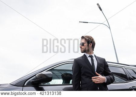 Low Angle View Of Bearded Bodyguard In Sunglasses And Suit Standing Near Modern Car.