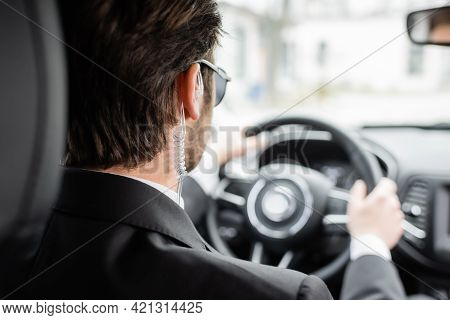 Back View Of Bodyguard Driving Modern Automobile.