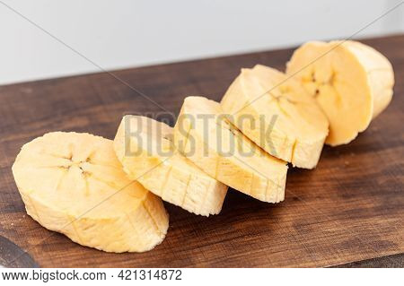 Closeup Ripe Plantain Pieces Over A Wooden Cutting Board