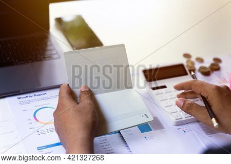 Business Accountants Or Bankers Open Passbooks And Calculate Savings Money, Financial And Tax, Costs