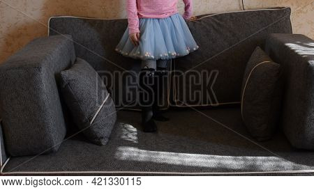 Toddler Girl In Light Blue Tulle Tutu Skirt Stand On Couch With Pillows. Legs Of Girl Kid At Home