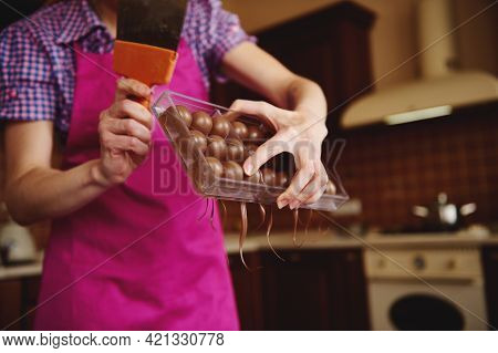 Closeup Of Chocolatier Making Shells For Chocolate Pralines And Removing Excess Chocolate From Molds