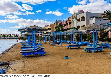 Umbrellas And Chaise Lounges On Beach In Hurghada City, Egypt