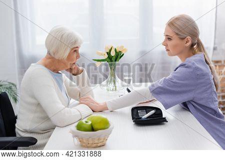 Side View Of Nurse Touching Hand Of Senior Diabetic Woman Near Insulin Pen Syringe.
