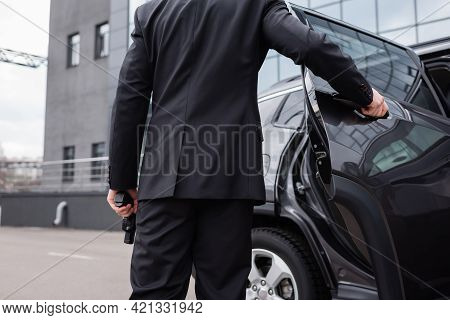 Back View Of Bodyguard In Suit Holding Gun And Opening Car Door.