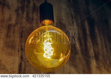Hanged Vintage Glowing Light Bulb. Retro Incandescent Lamp.