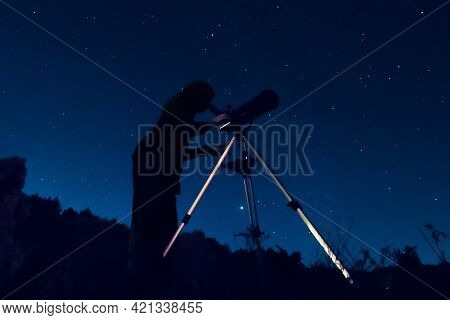 Dark Silhouette Of A Sky Watcher Of The Starry Sky In A Telescope. Woman Observer Watching The Night