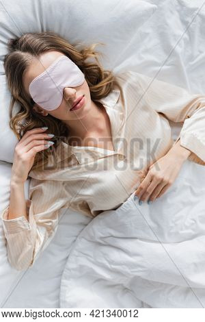 Top View Of Woman In Sleeping Mask And Pajama On Bed.
