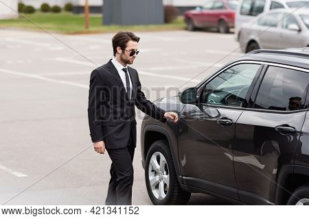 Bearded Bodyguard In Suit And Sunglasses With Security Earpiece Walking Near Modern Car.