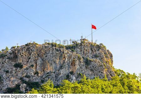 View On Chalish Mountain And Turkish Flag On Summit Not Far From City Kemer. Antalya Province, Turke