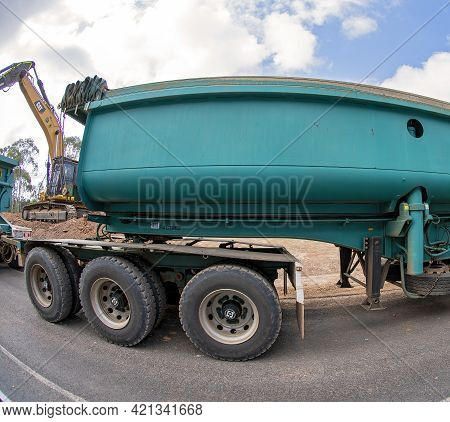 Clermont, Queensland, Australia - May 2021: Cargo Trailer Being Hauled Along Roadworks With Digger M