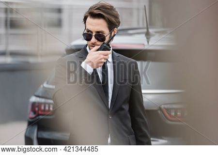 Bodyguard In Sunglasses And Suit Using Modern Walkie Talkie Near Blurred Car.