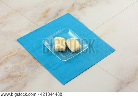 Two Mastic Toffee Candy Pieces In Transparent Candy Dish On Blue Napkin On Table