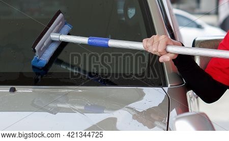 Gas Station Worker Cleaning The Car Windshield With Window Squeegee.