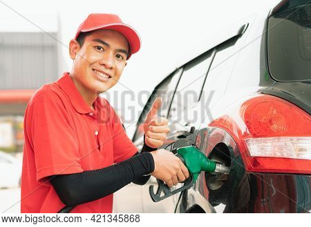 Asian Gas Station Worker Man Give Thumbs Up In One Hand And Holding Green Fuel Nozzle Into One Hand