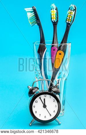 Alarm Clock And Glass With Toothbrushes On Blue.