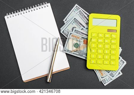 Notepad With Calculator And Money On The Black Background. Top View.