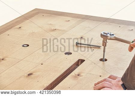 Skilled Craftsman Assembles Large Wooden Dining Table Turning Bolts With Wrench Outdoors On Sunny Da