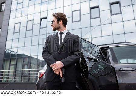 Low Angle View Of Bearded Bodyguard In Suit Holding Gun Near Car.