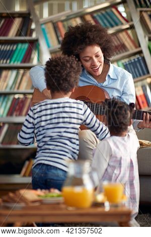 Young Mom sings and plays the guitar for her children in a relaxed atmosphere at home. Family, together, love, playtime