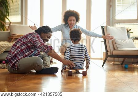 A happy parents spending quality time with their son while playing on the floor in a cheerful atmosphere at home. Family, together, love, playtime