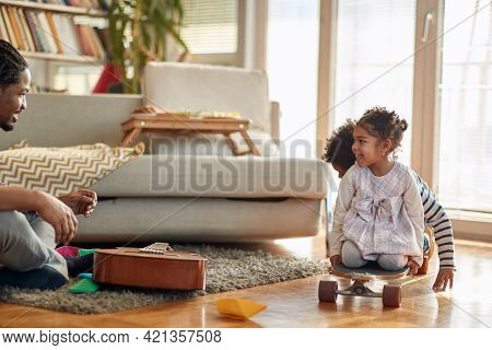 Kids enjoying playtime with their father in a cheerful atmosphere at home. Family, together, love, playtime