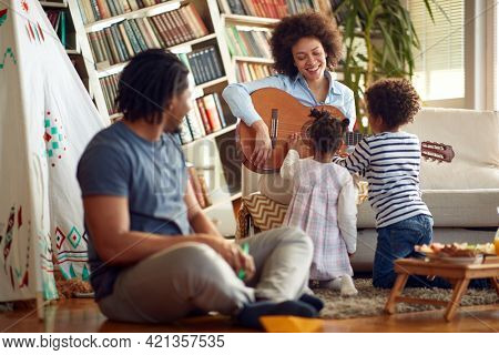 Kids love when Mom plays the guitar in a cheerful atmosphere at home. Family, together, love, playtime