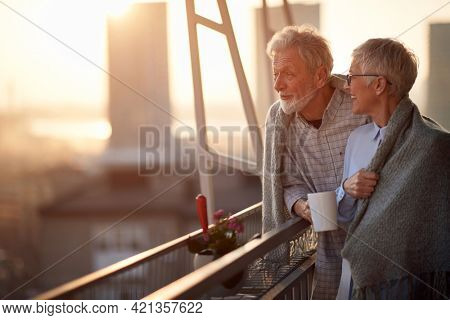 An elderly couple enjoying a view on the city from the terrace of their apartment at a beautiful sunset. Spouses, pensioners, together, home