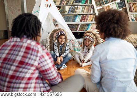 A happy family is sitting and chatting on the floor in a relaxed atmosphere at home while imitating Indians. Family, together, love, playtime