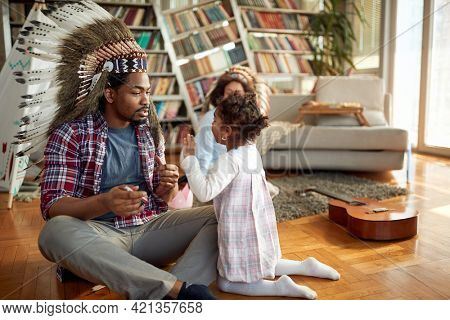 A young Dad with an indian headdress enjoys playing on the floor with his little daughter in a cheerful atmosphere at home. Family, together, love, playtime