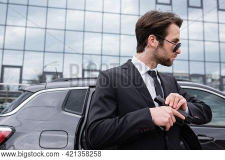 Bearded Bodyguard In Sunglasses And Suit Holding Gun Near Modern Building.