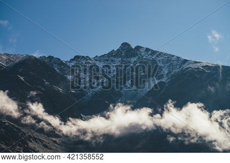 Wonderful View Of Rocky Mountain Wall With Snow Above Clouds And Peaked Top. Scenic Mountain Landsca