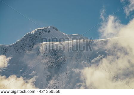 Minimalist View Of Snow-capped Mountain Wall In Thick Low Clouds In Sunshine. Scenic Bright Mountain