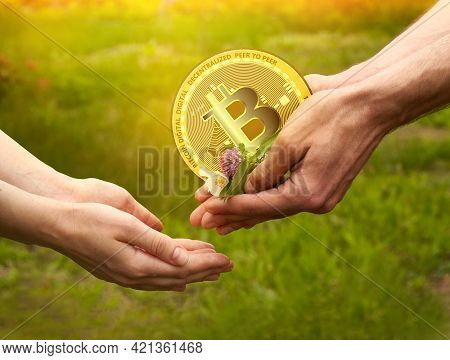 A Man Gives Flowers And Cryptocurrency To A Woman. Flowers And Bitcoin Coin In The Hands Of Men. The