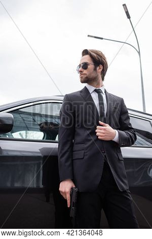 Low Angle View Of Bearded Safeguard In Sunglasses And Suit Standing Near Modern Car.