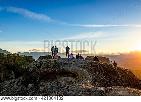 Meteora, Greece - May 16 2021: Incidental Young People Stand On The Summit And Enjoy The Sunset.