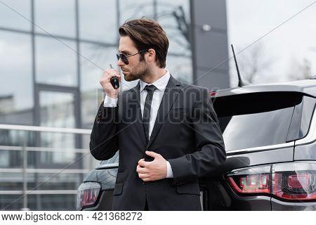 Side View Of Bodyguard In Sunglasses Using Walkie Talkie Near Modern Car.