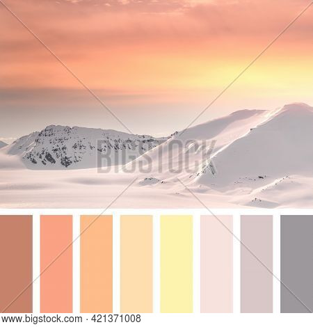 Scenic view of the pristine snow covered mountains at dusk, Svalbard, in a colour palette with complimentary colour swatches.