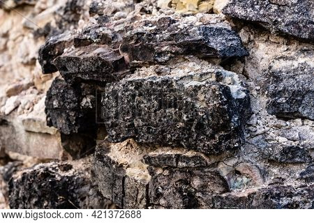 Close Up View Of Black Grey Stonewall Texture At Vecdole Castle In Latvia Built 1226 . Surface Of Ro
